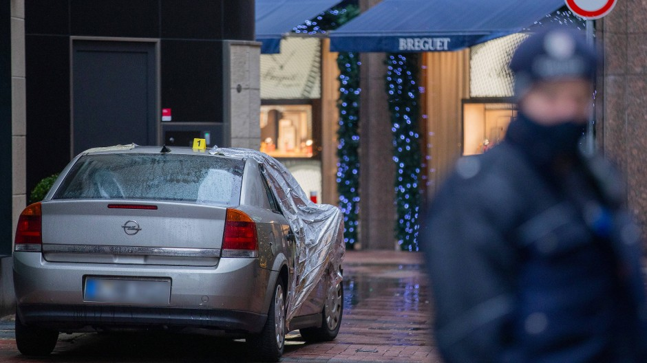 Polizeibeamte sichern nach einem Überfall den Tatort mit dem Tatfahrzeug vor einer Filiale der Schweizer Luxusuhrenmanufaktur Breguet hinter der Königsallee.
