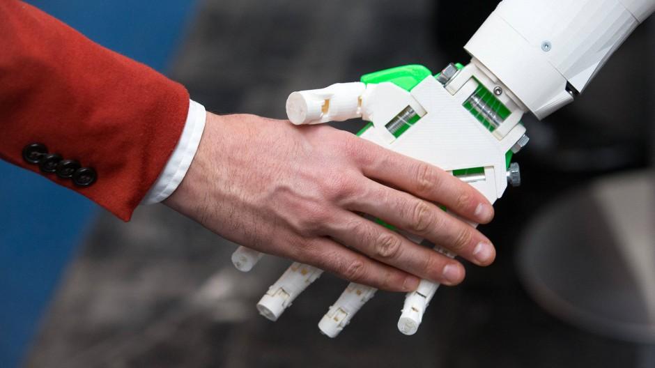 """Im Zeitalter der """"Handvergessenheit"""": Ein humanoider Roboter und ein Mensch begrüßen sich."""