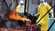 Helfer verbrennen die Kleidung von Ebola-Patienten