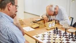 Blinde Schachspieler und Sportler auf Besen