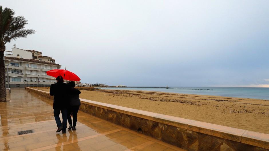 Ein Paar spaziert mit einem Regenschirm am Strand von Palma entlang.