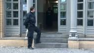Razzien und Beschlagnahmen: Polizist vor einem Haus in Berlin