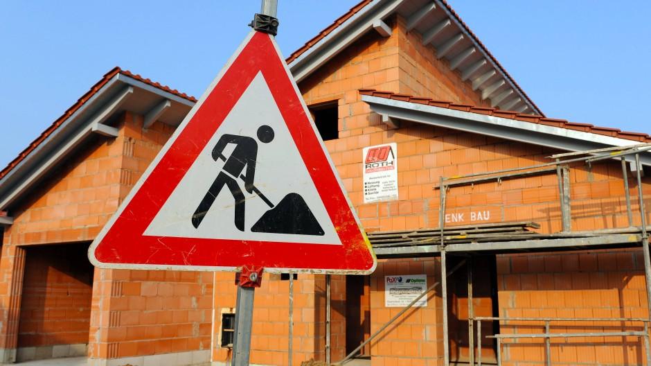 Erste Baustellen stehen still: Ein Baustellenschild steht vor dem Rohbau eines Einfamilienhauses (Archivbild).