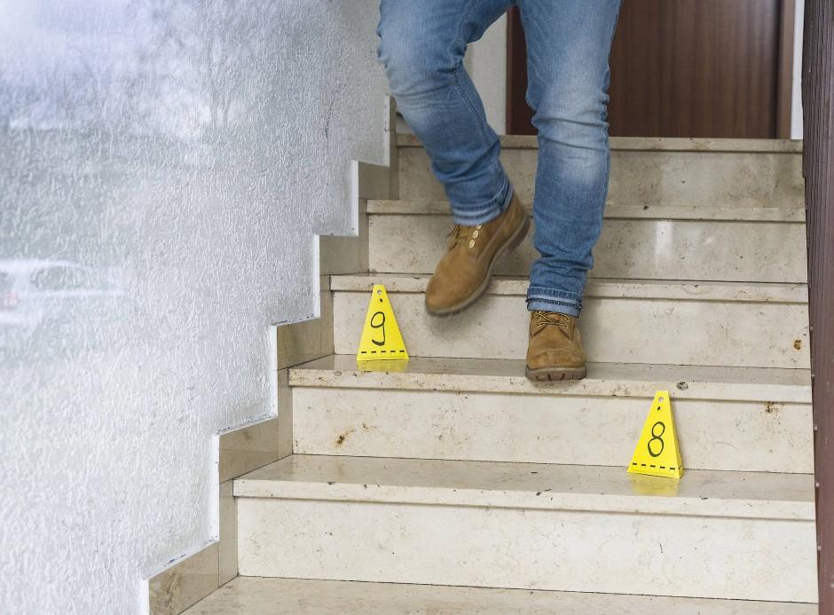 Tatort in Obertshausen: Ein Polizeibeamter geht in einem Hausflur an Markierungen der Spurensicherung vorbei.