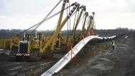 Mecklenburg-Vorpommern, Groß Polzin: Ein Pipeline-Stück der Erdgaspipeline Eugal wird mit Hilfe von Seitenbaumkränen bei Anklam ins Erdreich verlegt.