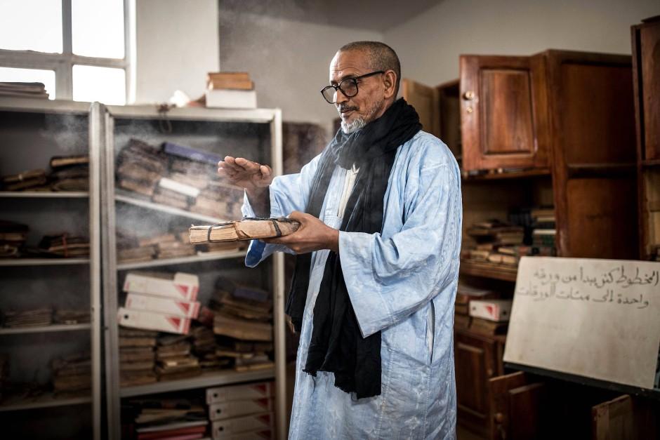 Moumhamedou Ahmadou, Direktor der Tichitt-Bibliothek und Übersetzer, wischt den Staub von einem alten Manuskript ab. Jahrhundertelang war Tichitt ein Zentrum der islamischen Kultur. Ahmadou pflegt und sammelt die alten Zeugen des Wissens.