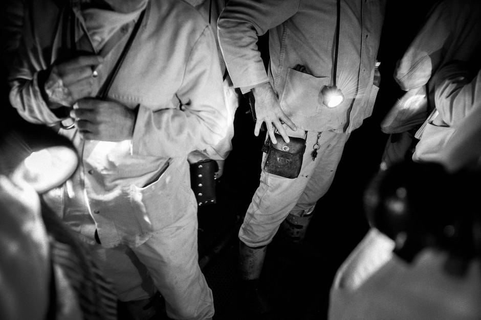 An einem Förderkorb, der an einem Seil hängt, werden die Bergleute in das Steinkohle-Bergwerk transportiert.
