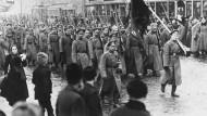 Diese Soldaten haben sich der Revolution angeschlossen. Sie marschieren mit roter Fahne auf dem Petersburger Newski-Prospekt, März 1917.