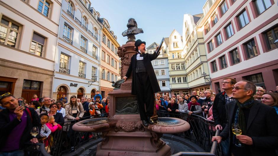 Ein Schauspieler der Fliegenden Volksbühne Frankfurt steht auf dem Stoltze-Brunnen und spricht zu den Besuchern des Hühnermarkts im Jahr 2018.