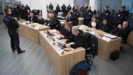 Diesseits des Plexiglasvorhangs: Die acht Angeklagten warten mit ihren Rechtsanwälten auf die Urteilsverkündung.