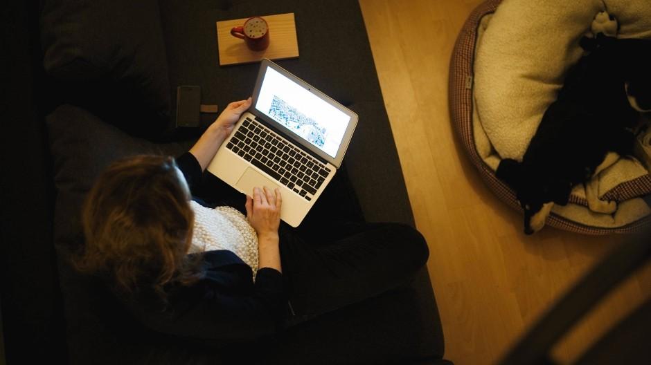 Eine Frau sitzt auf der Couch ihrer Wohnung und arbeitet am Laptop.