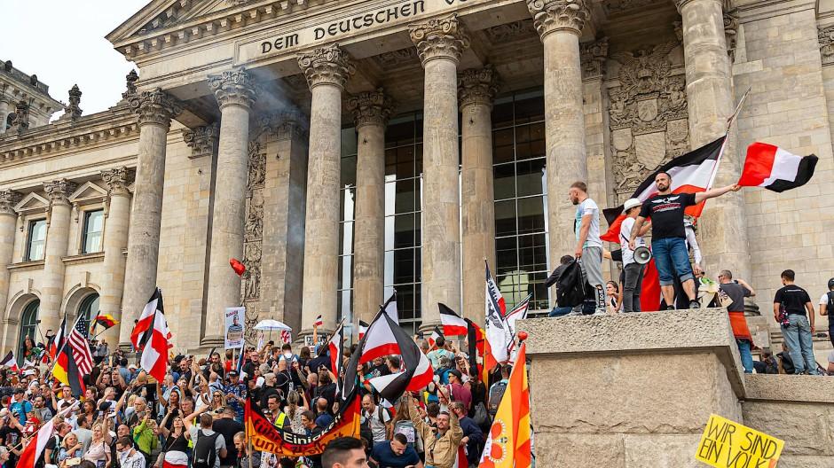 Teilnehmer einer Kundgebung gegen die Corona-Maßnahmen stehen Ende August 2020 auf den Stufen zum Reichstagsgebäude, Reichsflaggen sind zu sehen.
