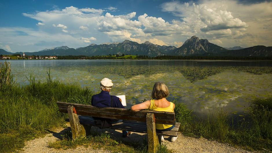 Ein älteres Ehepaar sitzt am Ostallgäuer Hopfensee bei Füssen.