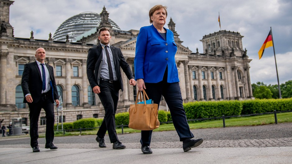 Bundeskanzlerin Angela Merkel geht am 13. Mai 2020 in Begleitung ihrer Personenschützer nach der Regierungsbefragung im Bundestag zu Fuß zum Kanzleramt.