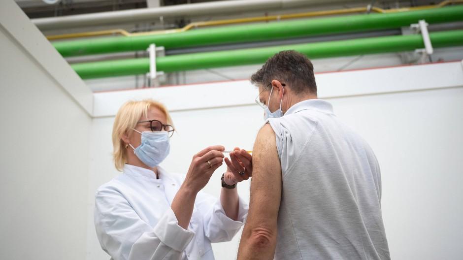 Eine Betriebsärztin im Opel-Werk in Rüsselsheim impft einen Mitarbeiter.
