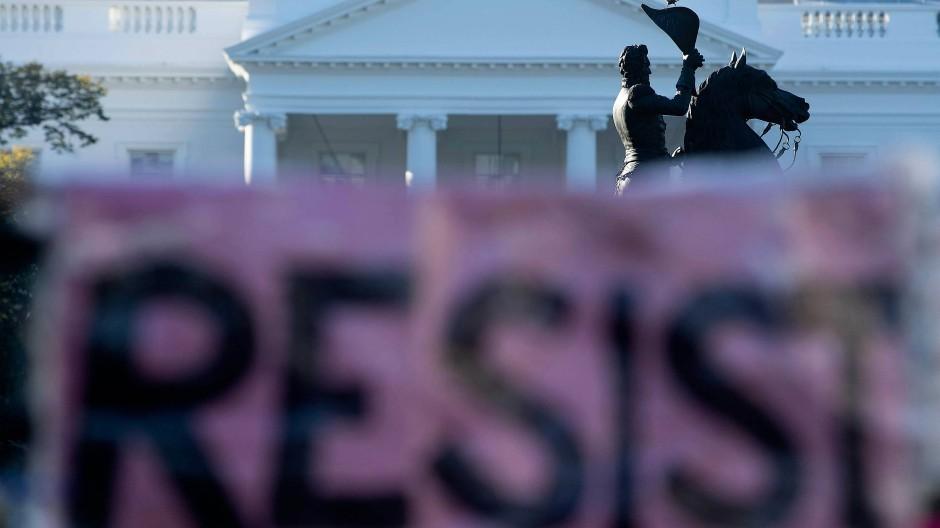 """Protestierende haben den Schriftzug """"Resist"""" am Zaun vor dem Weißen Haus angebracht."""