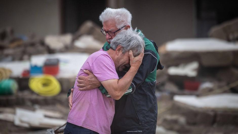 Altenahr in Rheinland-Pfalz: Weinend liegen sich zwei Brüder vor ihrem von der Flut zerstörten Elternhaus in den Armen.