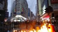Demonstranten legen ein Feuer auf einer Straße in Hongkong, um den Verkehr lahmzulegen.