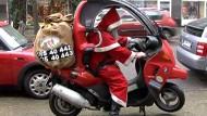 Ein Weihnachtsmann auf dem Motorroller