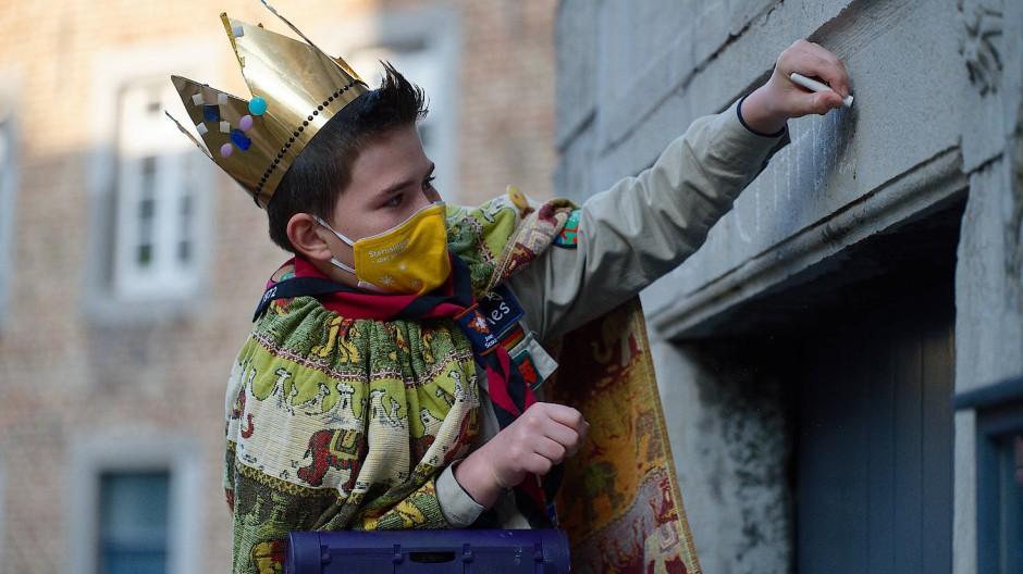 Der Sternsinger Hannes (11) schreibt den Segenspruch mit Kreide über ein Portal am Aachener Dom.