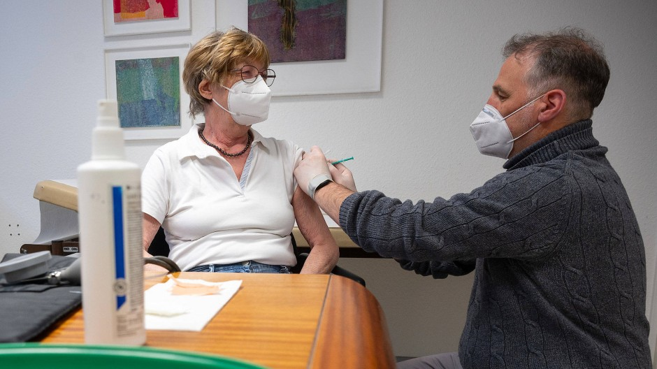 Nun möglich: Ein Arzt impft eine Frau in einer Wiesbadener Hausarztpraxis mit dem Impfstoff von Biontech.