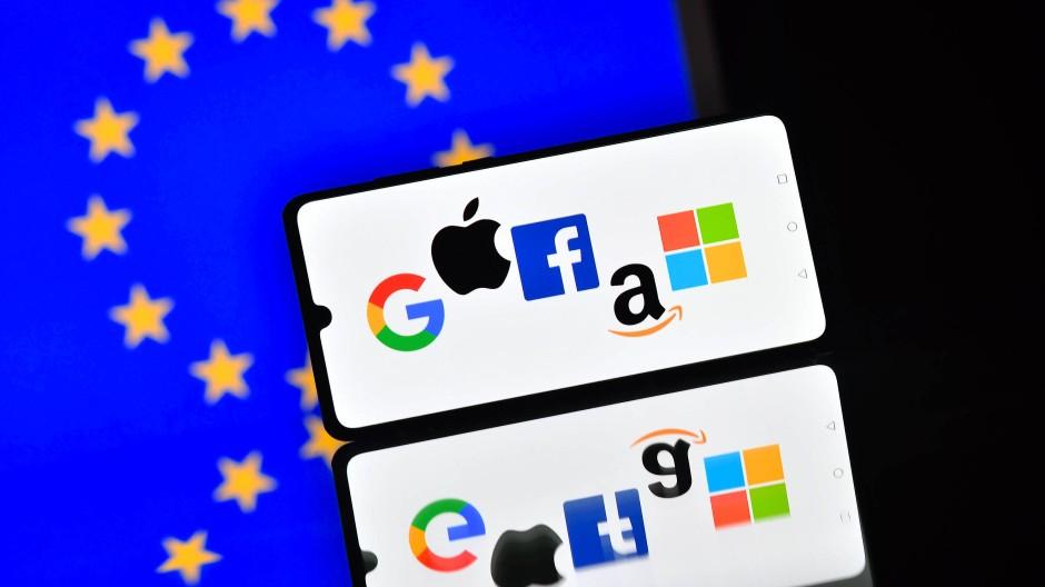 Die Logos von Google, Apple, Facebook, Amazon und Microsoft auf einem Smartphone mit der Europaflagge im Hintergrund. (Symbolbild)