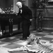 """Butler James, gespielt von Freddie Frinton, schaut in """"Dinner for one"""" mißbilligend zu dem auf dem Boden liegenden Tigerfell."""
