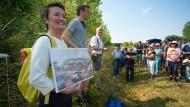 Die Frankfurter Umweltdezernentin Heilig zeigt ein historisches Foto der Mülldeponie.