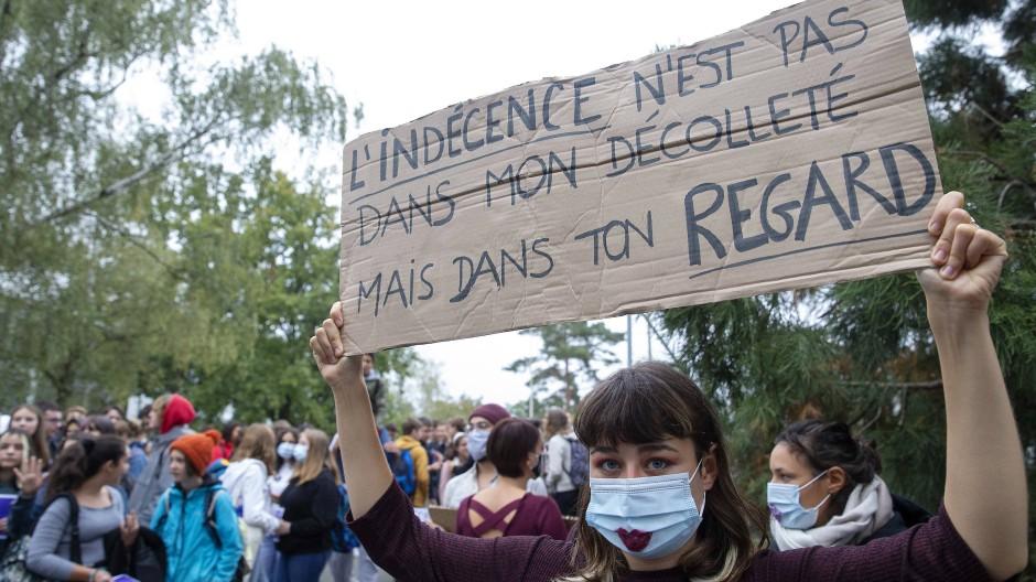 """Eine Schülerin hebt bei einer Demonstration vor dem Pinchat-Gymnasium ein Plakat mit der Aufschrift """"Die Schamlosigkeit liegt nicht in meinem Dekolleté sondern in deinem Blick"""" hoch."""