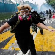 Ein Student in Hongkong, der vor einem Polizisten wegläuft.