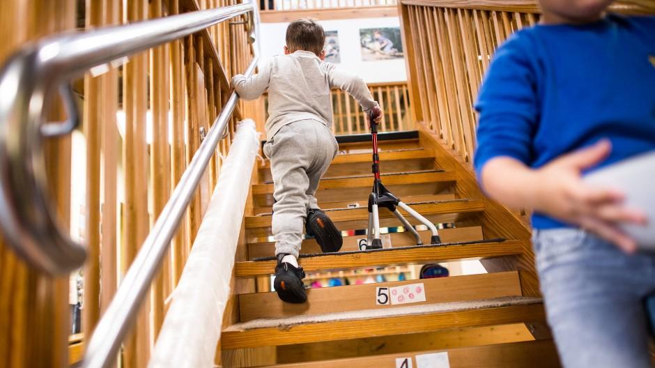 Ein Kind geht mit Gehhilfe eine Treppe hinauf.