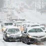 Fahrzeuge stehen während eines Schneesturms in Amerika im Stau.