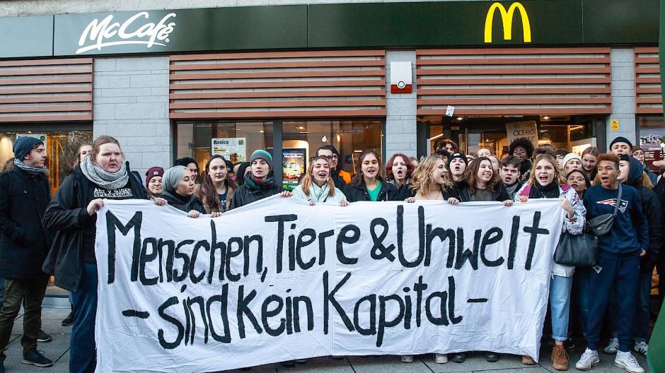Protest vor dem McDonalds: Umweltaktivisten demonstrieren gegen Konsum und Wegwerfgesellschaft.
