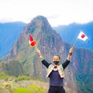 Jesse Katayama mit der peruanischen und japanischen Flagge, nachdem er als einziger Tourist die Inkastadt besuchen durfte.