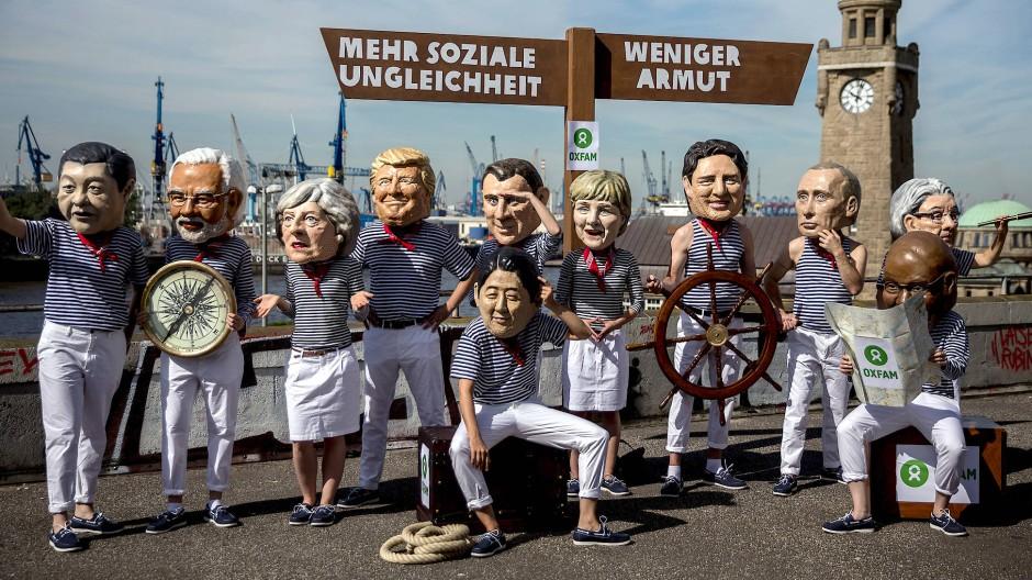 Aktivisten von Oxfam weisen bei einer Aktion in Hamburg 2017 mit einer symbolischen Kreuzung auf den Abzweig zwischen mehr sozialer Ungleichheit und weniger Armut hin.