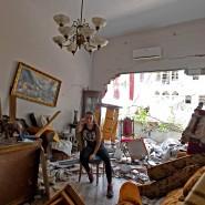 Eine Frau sitzt zwei Tage nach den Explosionen im Hafen von Beirut in ihrer zerstörten Wohnung. Die Wucht der Detonationen ließ Fenster bersten und drückte Türen aus den Angeln.