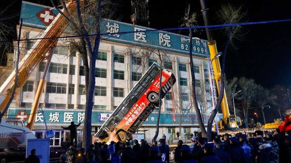 Erdrutsch auf chinesischer Straße: Schaulustige bestaunen die aufwändige Bergung des Busses aus dem Straßenloch in der Provinz Qinghai.