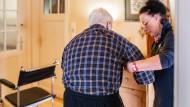Pflegefachkraft stützt einem Senioren beim Gehen.