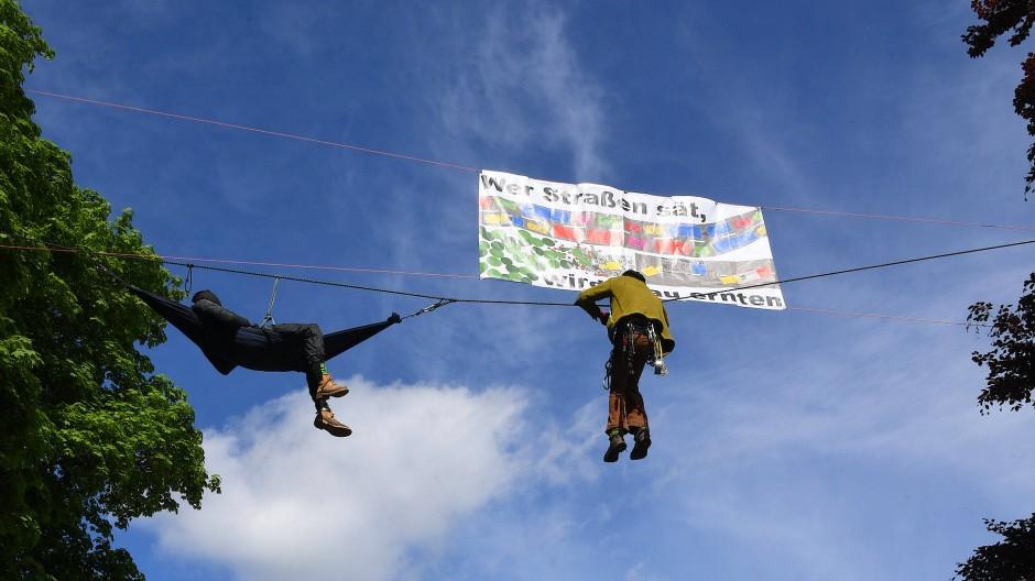 """Ein Klimaaktivist hängt über der Bundesstraße 32 an einem Seil, über ihm ein Plakat """"Wer Straßen sät, wird Stau ernten""""."""
