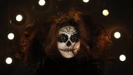 Viel Schminke gehört an Halloween dazu: Ein Partygast im französischen Nizza schwebt als Gespenst ein.