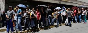 Menschen stehen vor einem Supermarkt in Caracas Schlange.