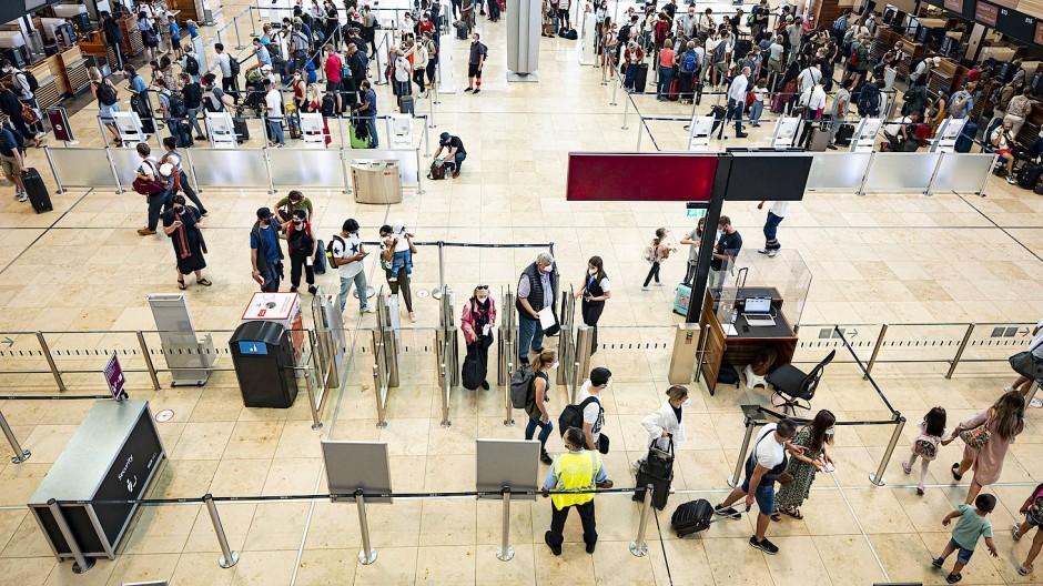 Fluggäste warten in der Haupthalle des Flughafens Berlin Brandenburg (BER).