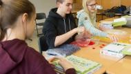 """Heimatverbunden: """"Mitarbeiter"""" der Schülerfirma Regames verpacken die Brettspiele."""