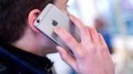 Ein junger Mann steht in einer Stadtbahn und telefoniert dabei mit seinem Smartphone. Handyverträge sollen künftig höchstens ein Jahr lang laufen.