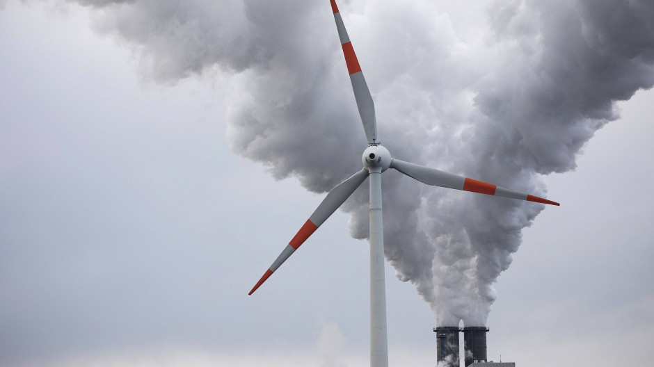 Abluft steigt aus den Schornsteinen des Kohlekraftwerks Moorburg hinter einem Windrad in den Himmel.