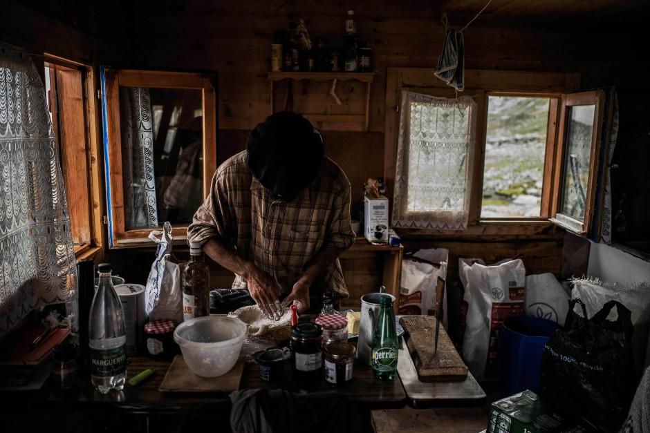 Meme bereitet in seiner Hütte sein Essen vor.