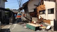 Rettungskräfte zwischen zerstörten Häusern in Kumamoto.