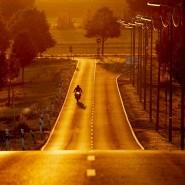 Ein Motorradfahrer während des Sonnenaufgangs am Stadtrand von Frankfurt am Main.