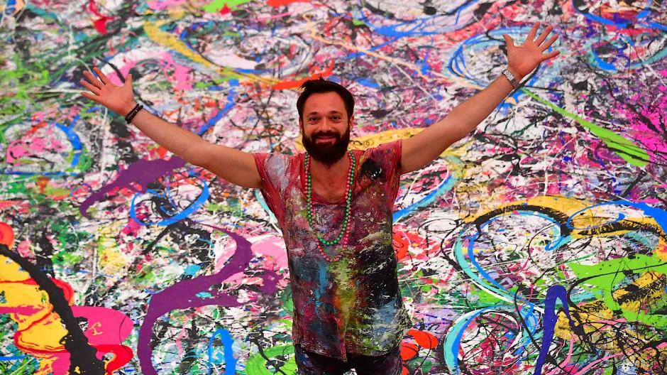 """High-Society-Maler und Spendensammler: In beiden Disziplinen ist Sacha Jafri extrem erfolgreich. Hier posiert er auf seinem Riesengemälde """"The Journey of Humanity""""."""