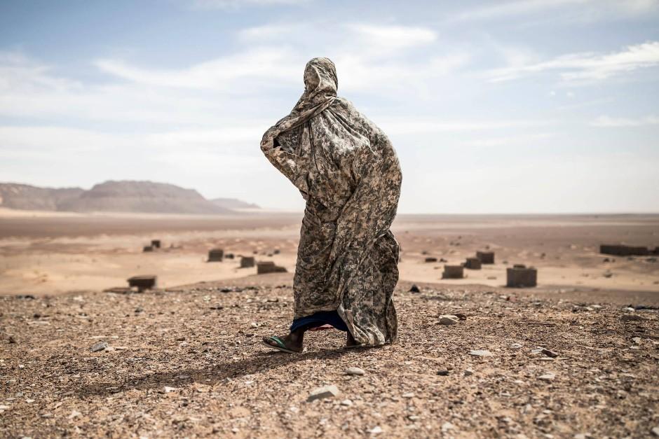 Eine Frau, vor der Sonne geschützt, spaziert durch die Wüstenumgebung der neolithischen Handelsstadt Tichitt.